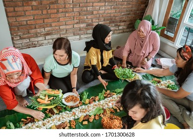 asian muslim woman preparation for dinner with friend at home. kembulan eating tradition