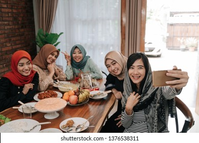 asian muslim woman wearing hijab take selfie together with smartphone