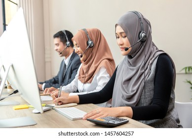 Asian muslim woman wearing microphone headsets working as customer care operator with team in call center office