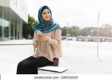 Asian muslim women wearing hijab listening to music with headset, having coffee break outdoor on city background