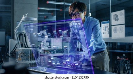 Asian Neural Microchip Design Engineer Uses Modern Computer With Transparent Holographic Display. Monitor Shows Advanced Technology Interface . Shot in Modern Glass and Concrete Office.