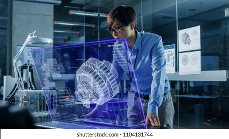 Asian Neural Network Engineer Uses Modern Computer With Transparent Holographic Display. Monitor Shows Visualization of a Mechanical Part. Shot in Modern Glass and Concrete Office.