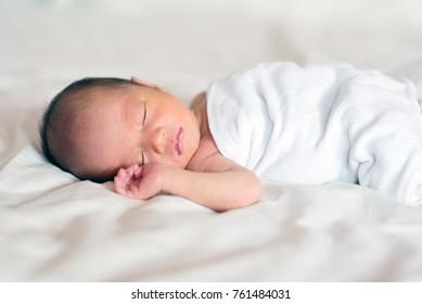 Asian newborn baby boy sleeping in white blanket, 7 days old.