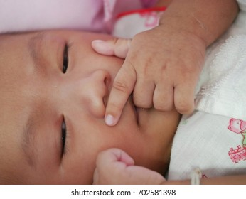 Asian newborn baby girl lying on bed, sleeping, close up