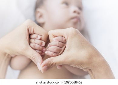 Asian newborn baby holding mother hands in heart shape, Closeup hand of asian newborn baby. copy space background banner family parents love mother's day concept