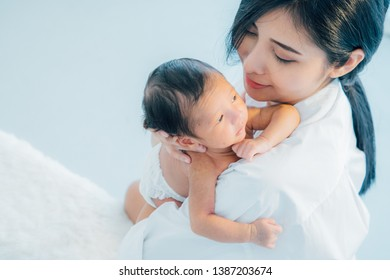 Asian newborn baby with mother concept : young mother breast feeds newborn in living room