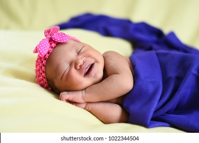 asian newborn baby on yellow background wrapped with blue cloth. life concept