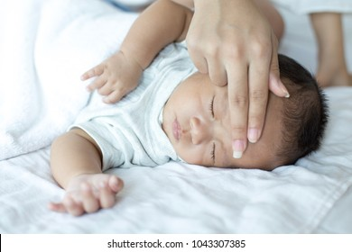 Asian newborn baby sleep  in bed. Mother mom touch baby head.
