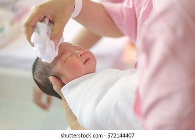 asian newborn bathing by his mother, baby boy