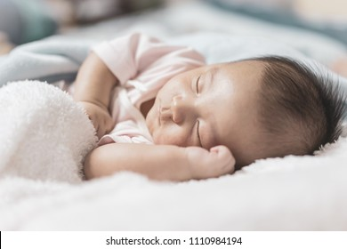 Asian newborn sleeping on white bed. New family, protection, relaxation and relationship concepts.
