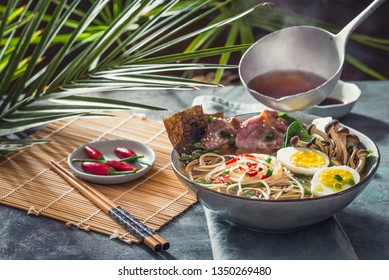Asian noodle in broth with meat and pickled egg in bowl on dark background.Ramen bowl and ladle with hot broth.