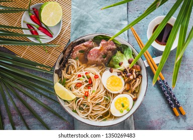 Asian noodle in broth with meat and pickled egg in bowl on dark background.Ramen bowl.