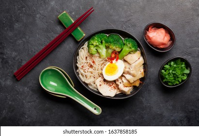 Asian noodle ramen soup with chicken, vegetables and eggs on stone background. Top view flat lay