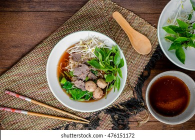 asian noodle soup with beef meatball with fresh vegetable on wood table vintage style, street food, hot and spicy noodle soup, asian food. Top view