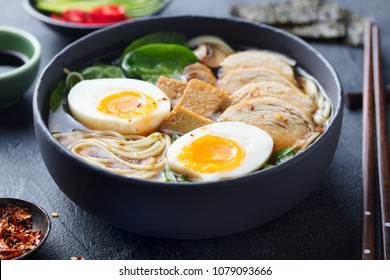 Asian noodle soup, ramen with chicken, tofu, vegetables and egg in black bowl. Slate background.