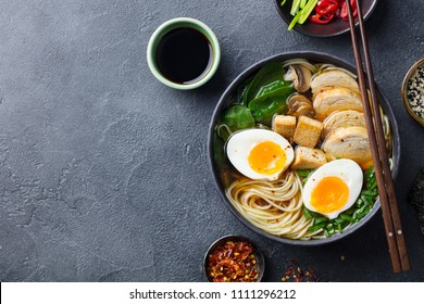 Asian noodle soup, ramen with chicken, tofu, vegetables and egg in black bowl. Slate background. Top view. Copy space.