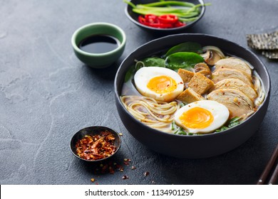 Asian noodle soup, ramen with chicken, tofu, vegetables and egg in black bowl. Slate background. Copy space.