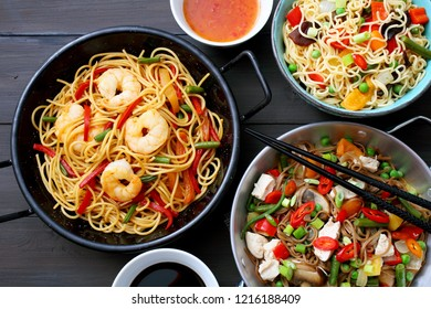 Asian noodles with chicken shrimp and vegetables on gray background
