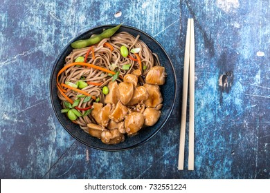Asian noodles with chicken, vegetables, bowl, rustic wooden blue background. Closeup. Top view. Soba noodles, teriyaki chicken, edamame, chopsticks. Asian style dinner/lunch. Chinese/Japanese noodles
