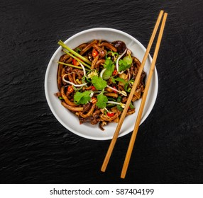 Asian noodles with spicy soy sauce and chicken pieces, top view, served on black stone.