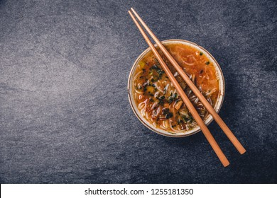 Asian noodles with vegetables and sticks on a dark background, top view with copy space