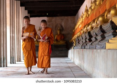 Asian Novice monks reading the holy book in the Buddhist temple in  Ayutthaya province, Thailand. A little novice monks learning the Buddhist scripture.