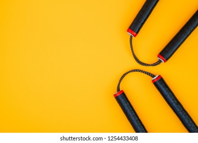 Asian Nunchaku weapon on a yellow background and a place for text. Flat lay
