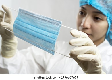 Asian nurse or doctor on personal protection equipment PPE inspecting a facemask.