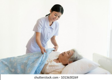 Asian nurse in elderly care cover her with a blanket for the elderly in nursing home. Elderly patient care and health lifestyle, medical concept.
