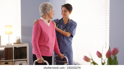 Asian nurse and elderly woman patient looking out window