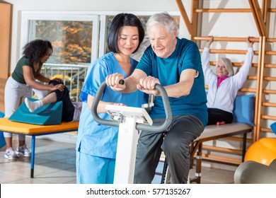 Asian nurse helping elder man in hospital gym.