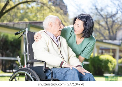 Asian nurse helping elderly man on wheelchair outdoor.