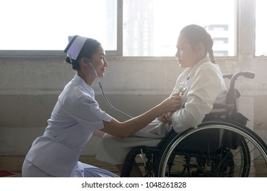 asian nurse  with patient in hospital wheelchair in corridor of specialist care clinic.