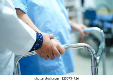 Asian nurse physiotherapist doctor care, help and support senior or elderly old lady woman patient walk with walker at hospital ward : healthy strong medical concept.
