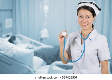 Asian nurse with stethoscope on background blur patient room.
