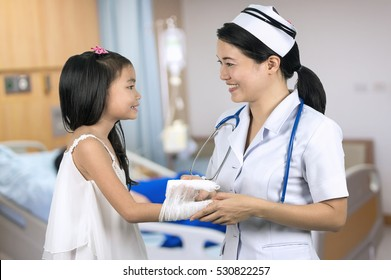 Asian nurse in uniform pediatric care girls with background blur patient room.