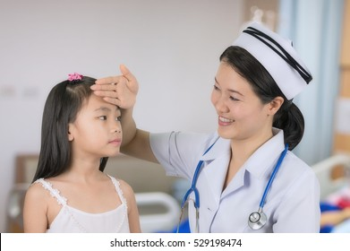 Asian nurse in uniform temperature measurements are girls with background blur patient room.