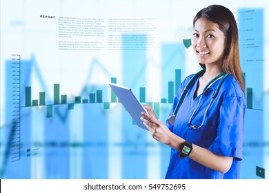 Asian nurse using tablet against business interface with graphs and data
