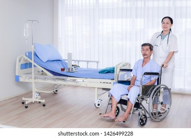 Asian nurses in white gowns are wheelchairs with elderly patients sitting out of the patient room.