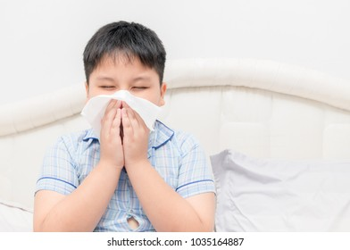 Asian obese fat boy blowing the nose by tissue, health care and sick concept