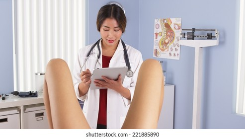 Asian OBGYN examining pregnant patient