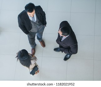 Asian office workers and foreign employees stand and talk in the office lobby.Top view.