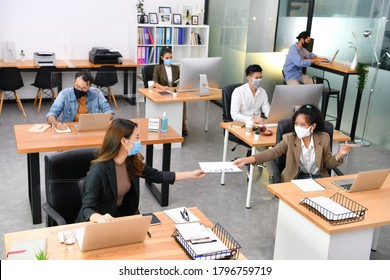 Asian office workers wearing face masks working in new normal office and doing social distancing during corona virus covid-19 pandemic