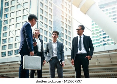 Asian office workers wearing a suit stand talking about doing business investment.