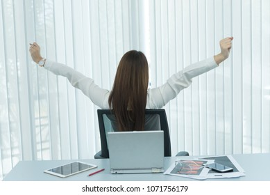 Asian officer woman stretching body at the desk of office from back angle,Thailand people,Businesswoman tired from hard work