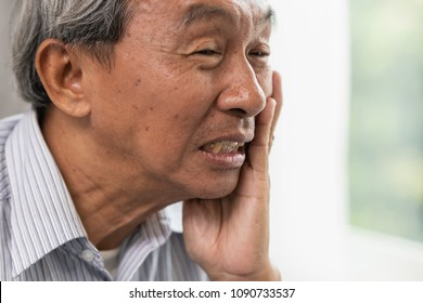 Asian Old man elder toothache pain suffer from dental problem teeth caries decayed tooth.
