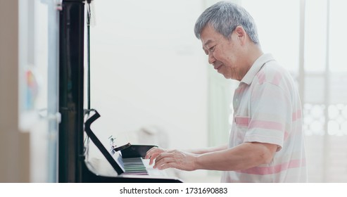 asian old man practice playing the piano at home
