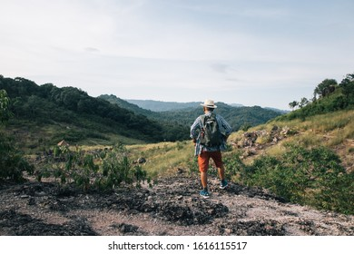 An Asian old man is searching for a path and a mountain to climb during the holidays with good weather. He comes with a backpack to use to rest on the way. Relax by the good weather and freedom.