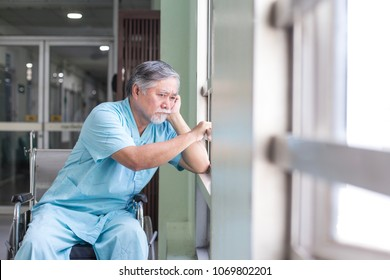 Asian old man sit on wheelchair looking out to other place. People with health care and medical concept.