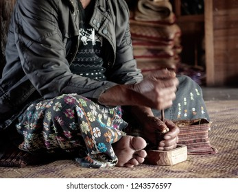 Asian old man sitting and pounding betel chewing betel leaves. Local ethnic village tribe member preparing betel. Old asian man in countryside, Indonesia - shaman, shamanism